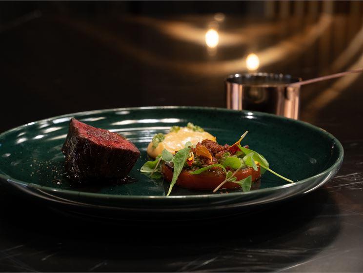 Danin paahdettua hanger steakia, karamellisoitua valkosipulipyrettä, meksikolaista salsa verdeä, grillattua tomaattia, rapeaa possun kylkeä ja chileillä maustettua lihalientä